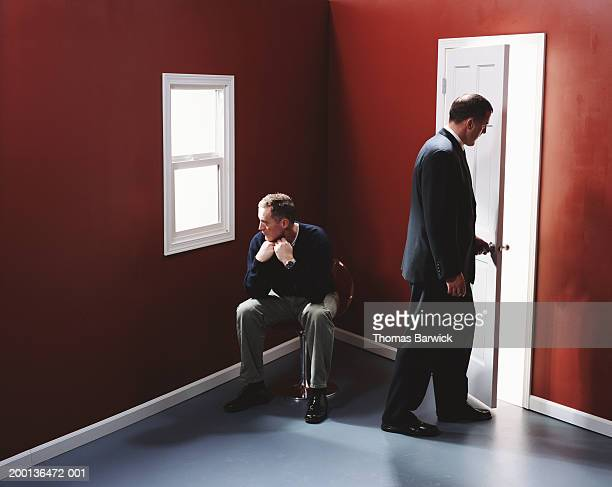 Two men in empty room, one by door, other seated looking out window