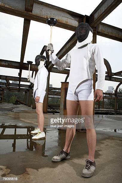 Two men in fencing gear standing in a urban industrial landscape holding plungers.