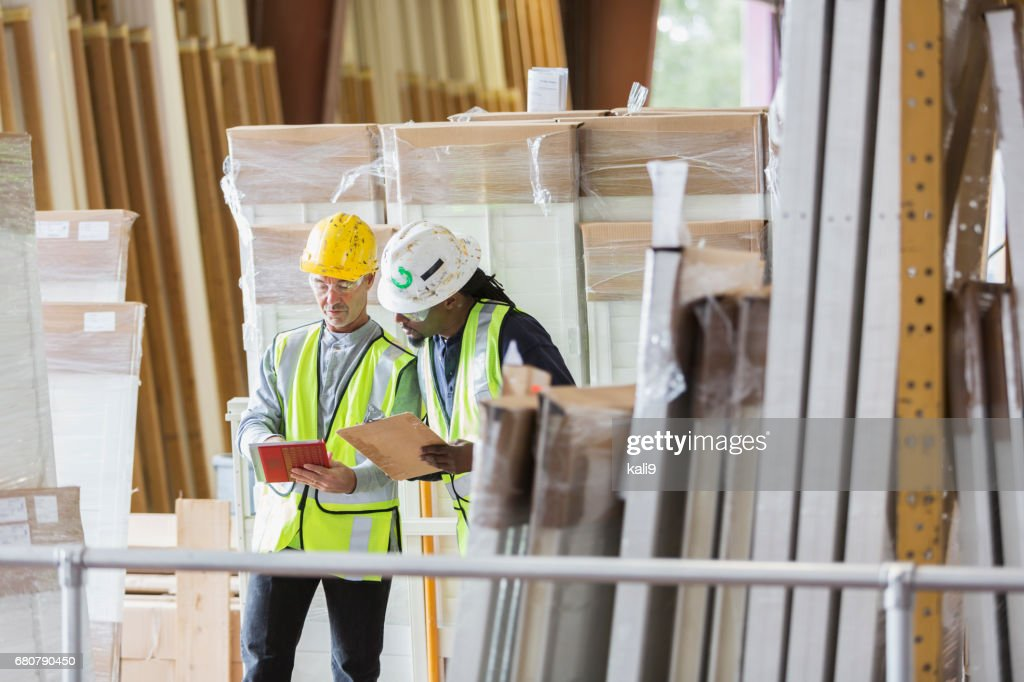 Two men in hardhats looking at warehouse inventory list : Stock Photo