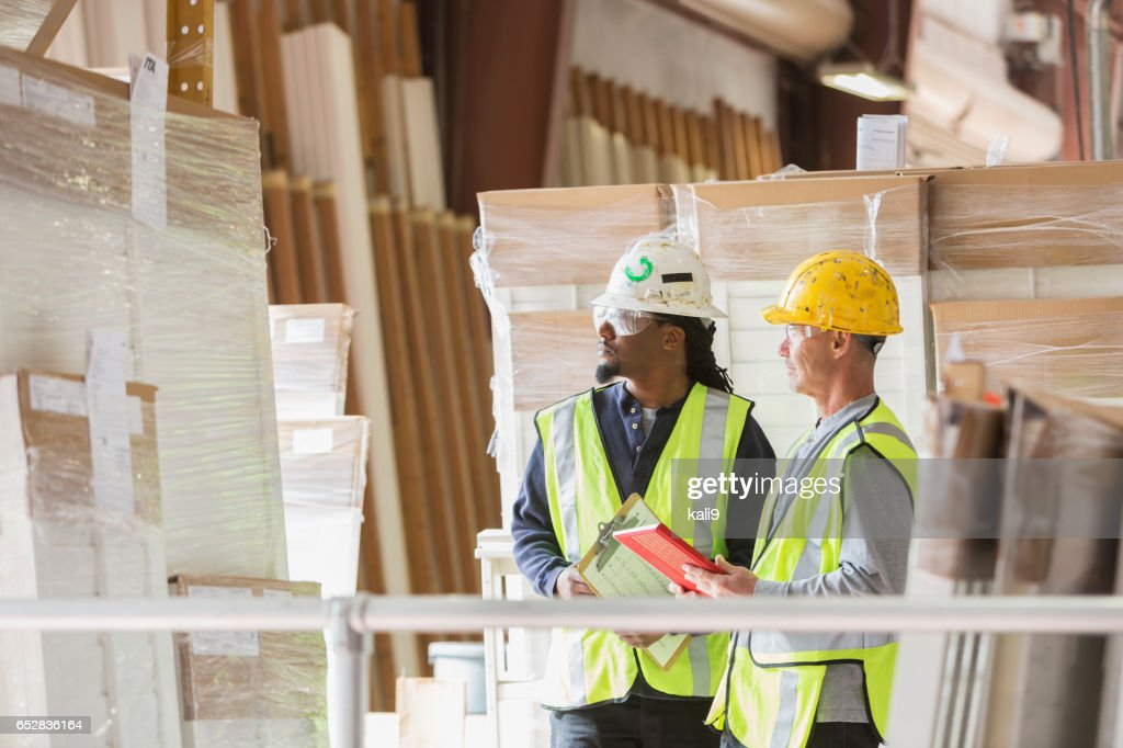 Two men in hardhats looking at warehouse inventory : Stock Photo