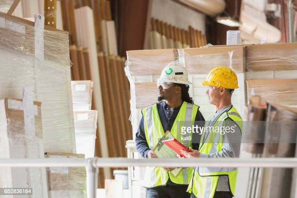 Two men in hardhats looking at warehouse inventory