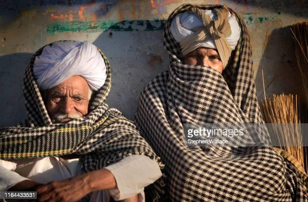 two men in india on cold day - only men stockfoto's en -beelden