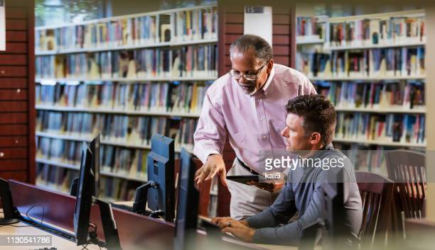 two men in library looking at computer screen - african american man helping elderly stock pictures, royalty-free photos & images