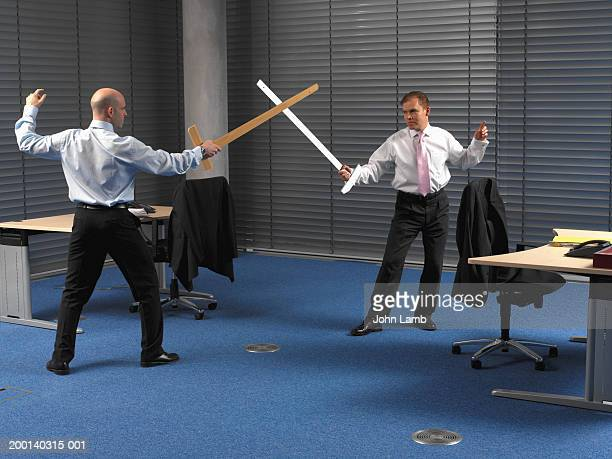 Two men in office, play sword fighting using large rulers