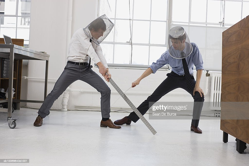 Two men in office, playing sword fighting using large rulers : Stock Photo