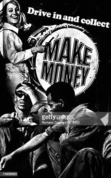 Two men in overalls sitting by an advertising poster depicting a smiling woman banging a bass drum London 1966