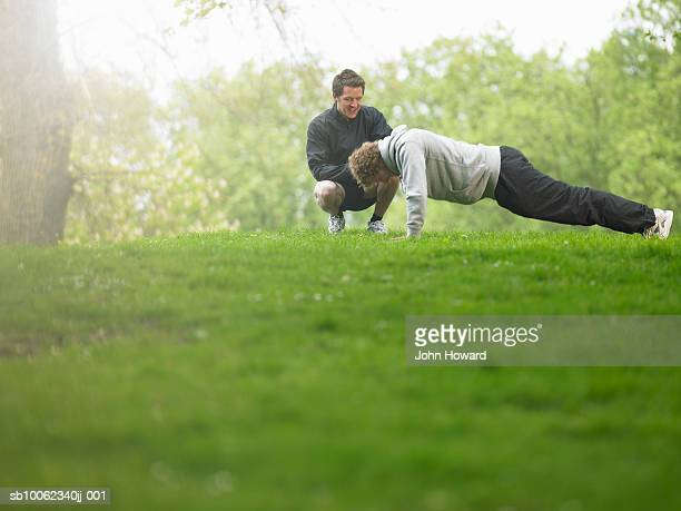 Two men in park, one doing push-ups other squatting and watching