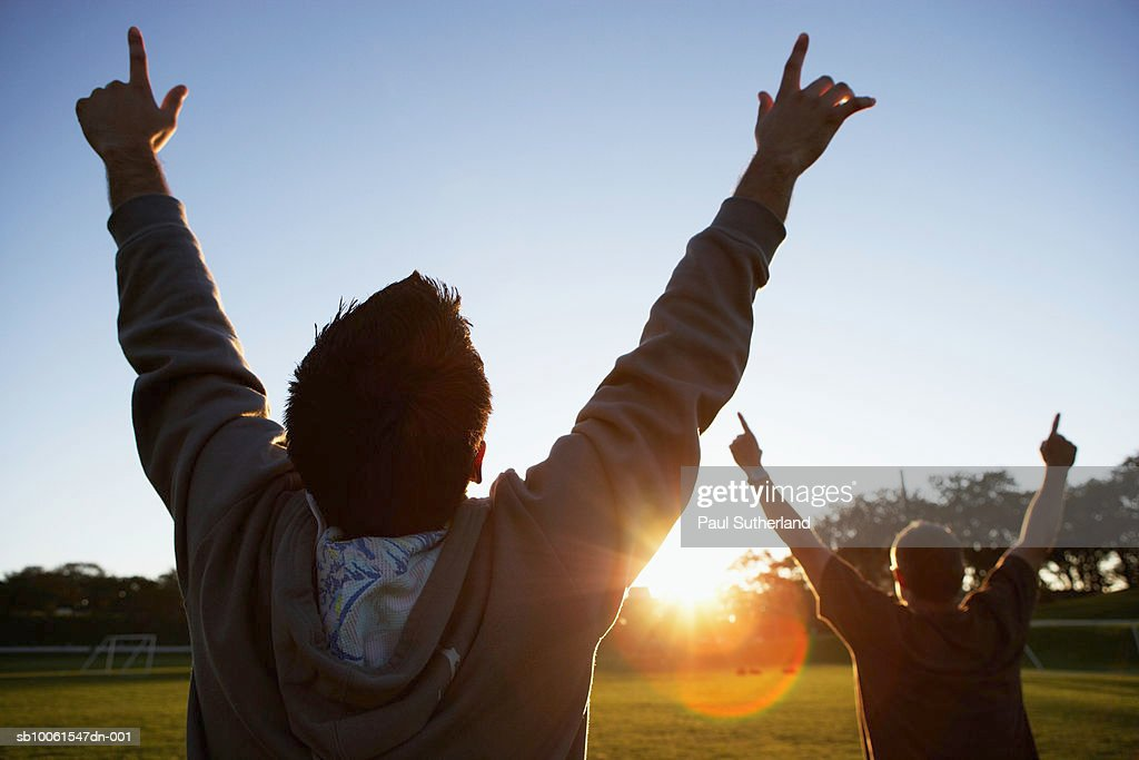 Two men in park, outstretching arms against sun, rear view : Stock Photo