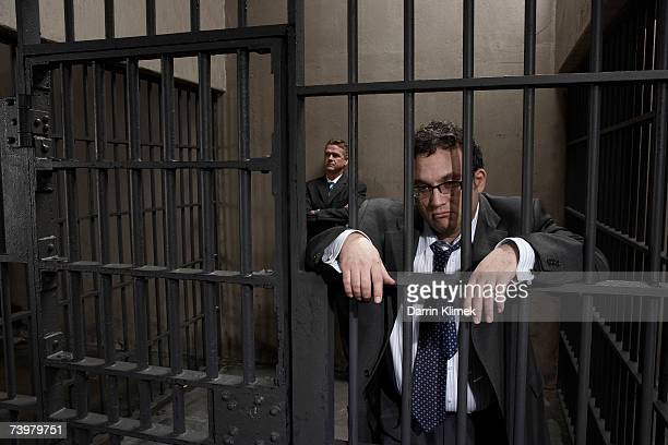 two men in prison cell, one leaning against bars - prisonnier photos et images de collection