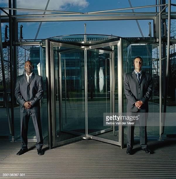 Two men in suits, standing either side of revolving door, portrait