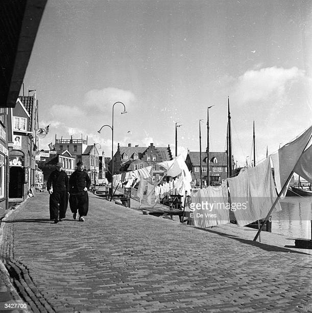 Two men in traditional baggy trousers walking through Volendam harbour in the western Netherlands