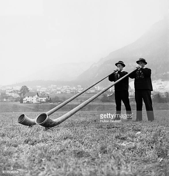 Two men in traditional Swiss dress stand in a grassy field blowing alpenhorns