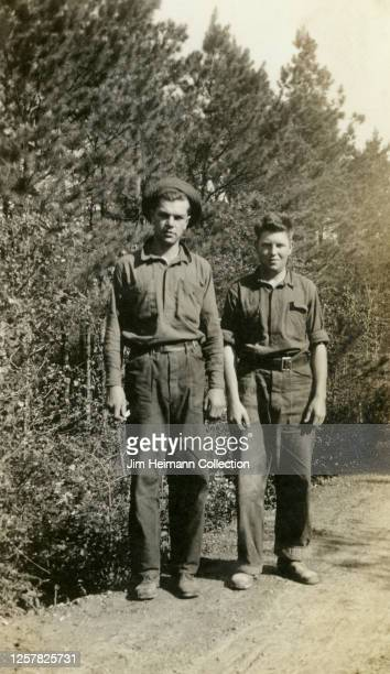 Two men in workwear pose side by side for a picture at Camp Flying Goose in Iowa, circa 1936.