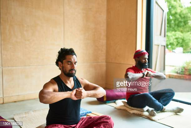 two men in yoga pose by open doorway - two people stock pictures, royalty-free photos & images