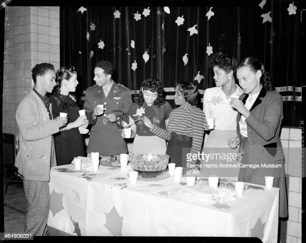 Two men including one on left wearing military uniform and five women posed behind table with punch bowl including Mary Jane Mitchell Page on right...