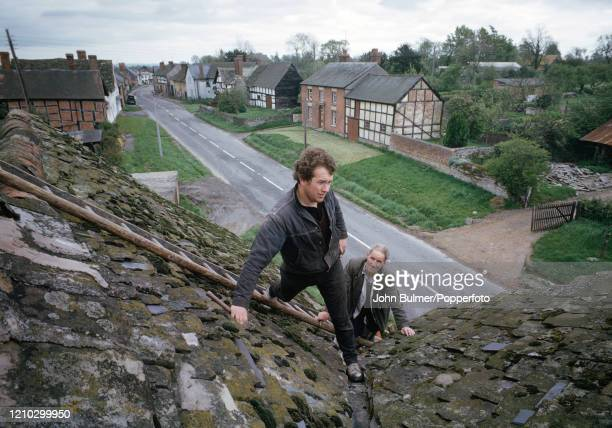Two men inspecting and repairing the moss and lichen-covered slate-tiled roof and guttering at an old house in Pembridge, England, circa June 1966....
