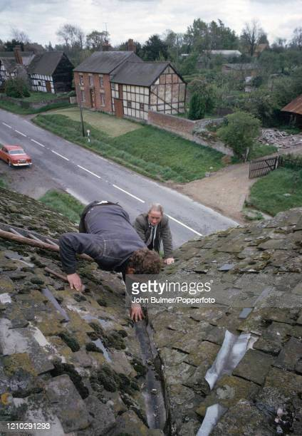 Two men inspecting the moss and lichen-covered slate-tiled roof and guttering at an old house in Pembridge, England, circa June 1966. During the...