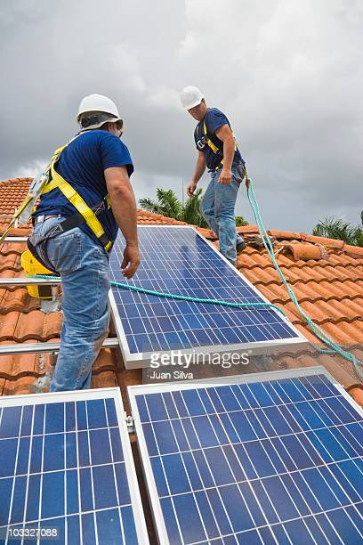 two men installing solar panel on house roof - roof tile stock pictures, royalty-free photos & images