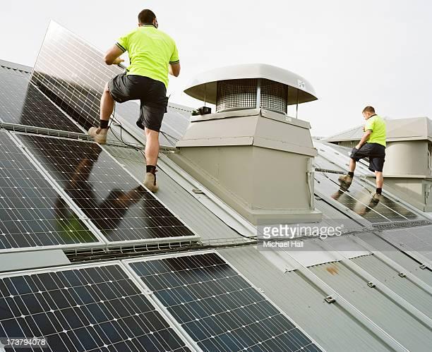 two men installing solar panels on roof - panel solar fotografías e imágenes de stock