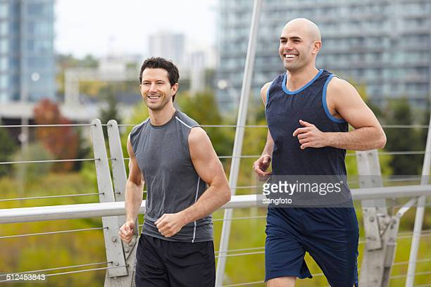 Two men jogging on the bridge smiling