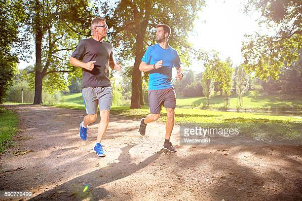Two men jogging together in a park