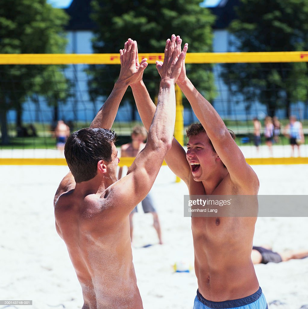 Two men joining hands above heads by beach volleyball net : Stock-Foto
