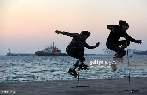 Two men jump as they skate on the embankment in Sevastopol on March 13 2014 The Ukrainian flag has never really been embraced in Sevastopol and its...
