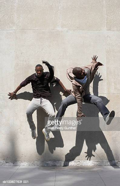 Two men jumping in front of wall