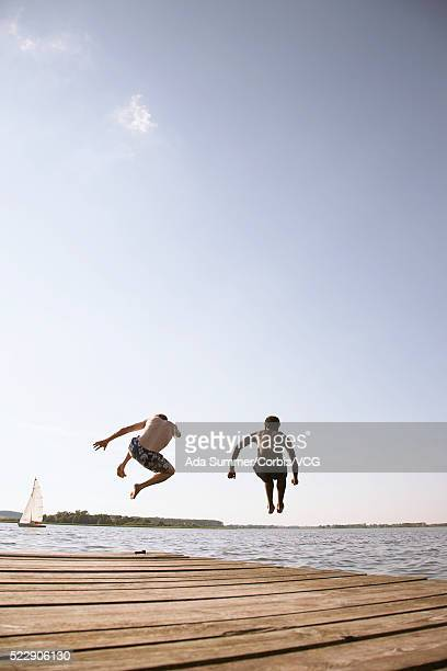 Two men jumping off dock