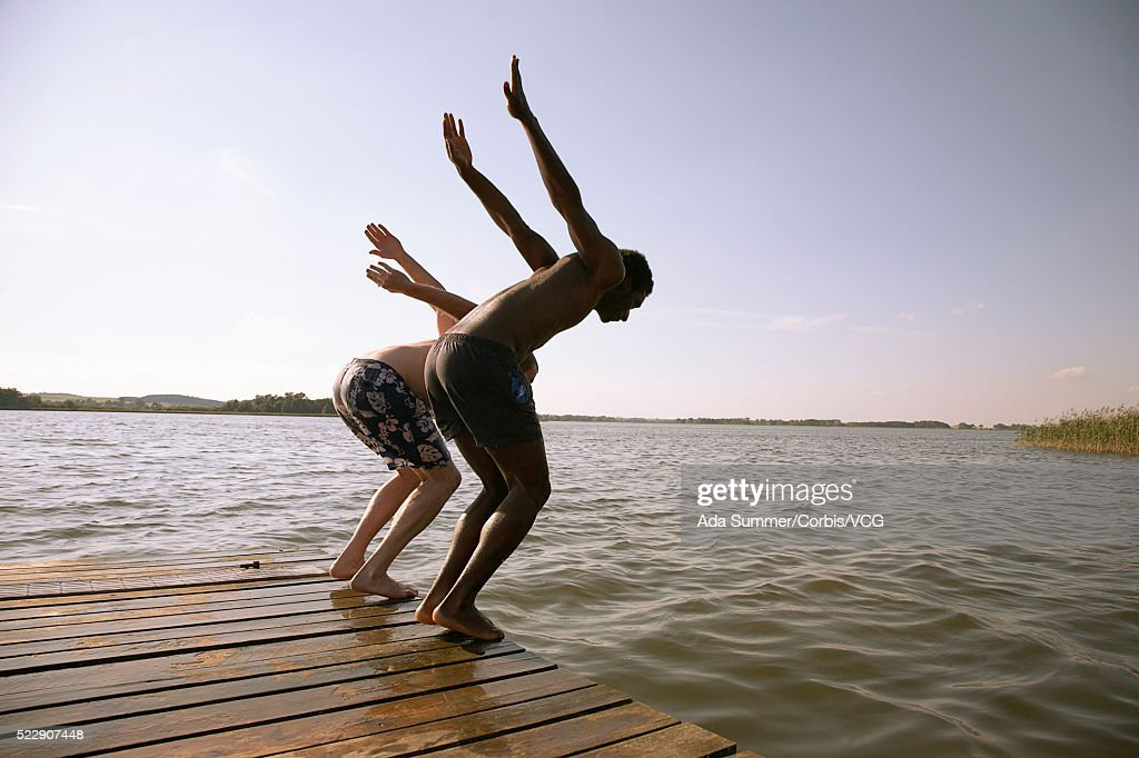 Two men jumping off dock : ストックフォト