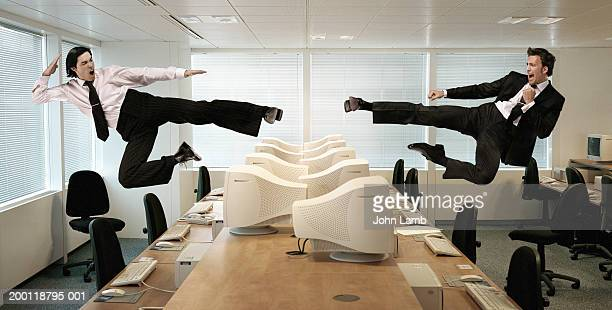 Two men kicking in mid-air across row of computers (Digital Composite)