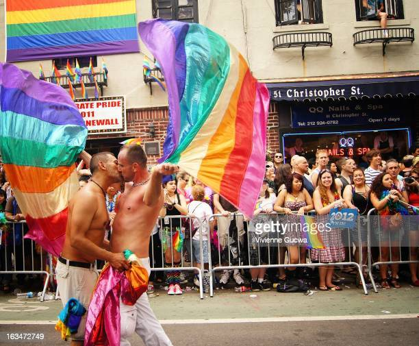 Two men kiss while twirling rainbow flags at the Gay Pride Parade in New York City in front of the Stonewall Inn on Christopher Street in the West...