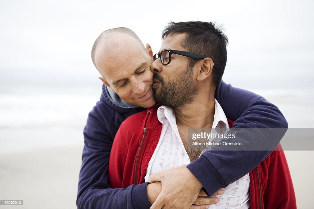 two men kissing on beach : Stock Photo