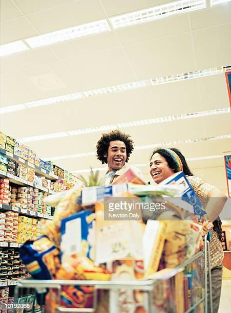 two men laughing in supermarket - caddie rempli photos et images de collection