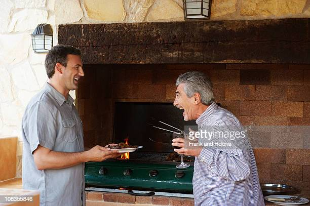 Two men laughing together by barbeque