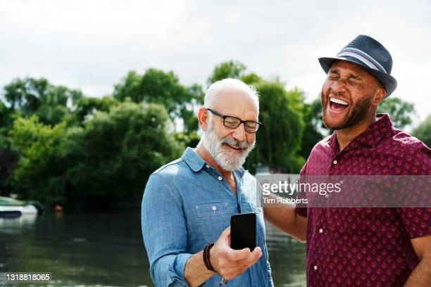 two men laughing with smart phone - summer stock pictures, royalty-free photos & images