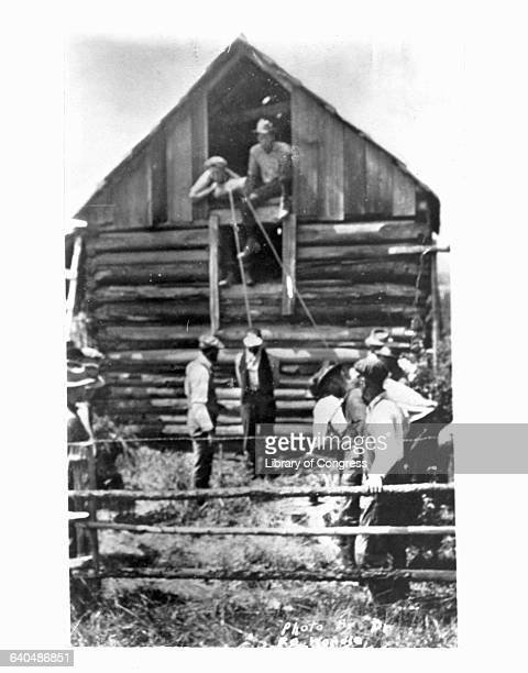 Two men lean out of a barn window above an African American man whose neck is tied in a noose and whose hands are tied behind his back. On the ground...