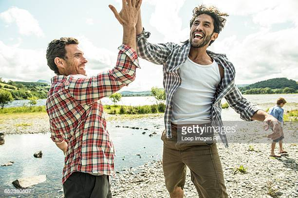 two men leaping to high five near bala lake in wales - high five stock-fotos und bilder