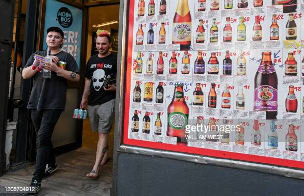 Two men leave a bottle shop displaying a sign showing dozens of beers for sale in Melbourne on March 31 after major alcohol retailers in the country...