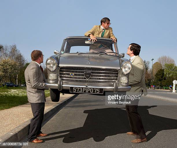 Two men lifting car with driver inside (Digital Composite)