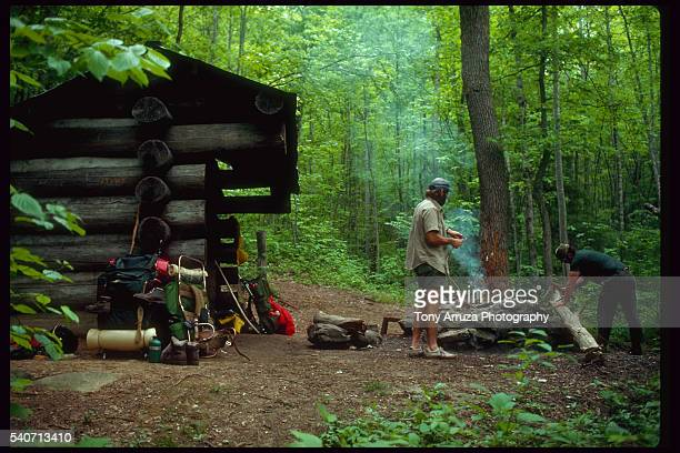 Two men light a fire outside a log cabin in a forest in North Carolina