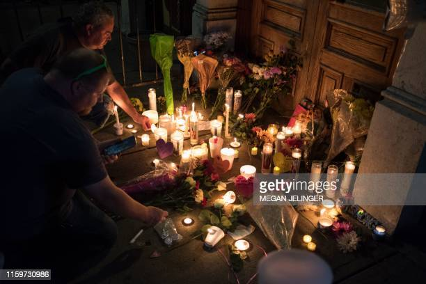 Two men light candles at a makeshift memorial as they take part of a candle lit vigil in honor of those who lost their lives or were wounded in a...