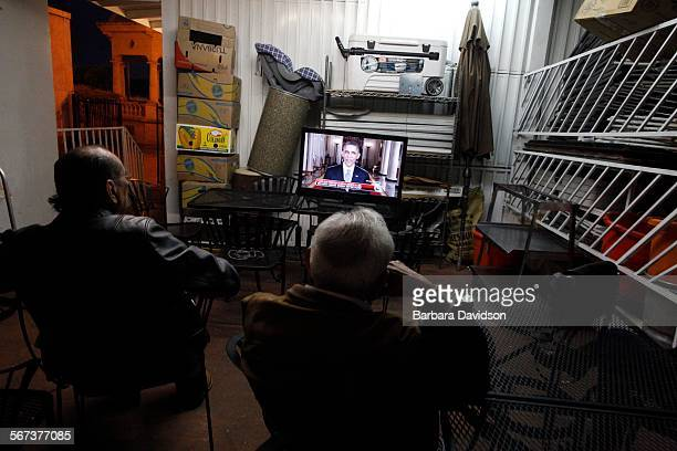 Two men listen to President Obama's speech on his executive action on immigration reform in a storage room at Restaurant Santa Cecilia in Los Angeles