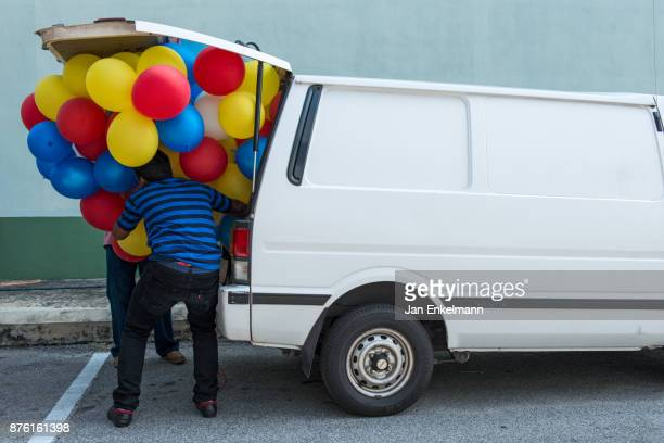 Two men loading balloons into a mini van