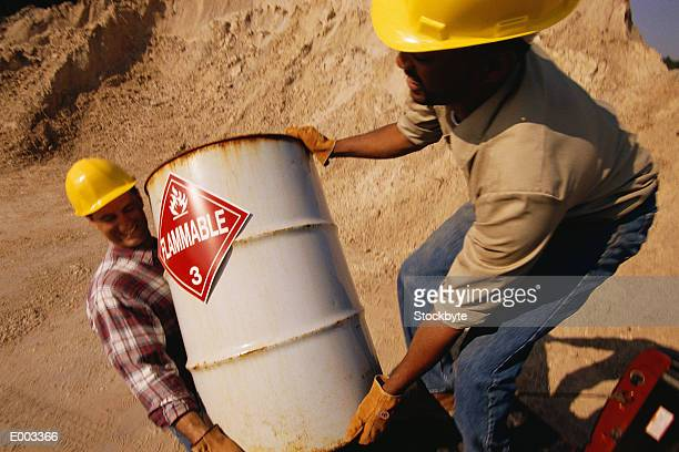two men loading barrel with flammable sign - flammable stock photos and pictures