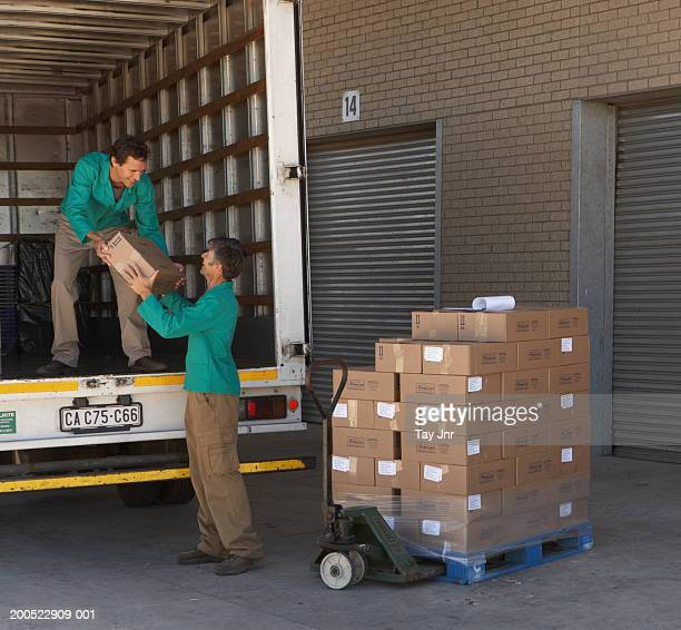 Two men loading boxes into lorry from pallet
