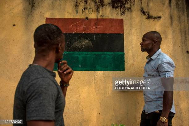 Two men look at a drawing of the Biafran flag on a wall in Umuahia one of the proBiafran separatist regions on February 13 ahead of Nigeria's...