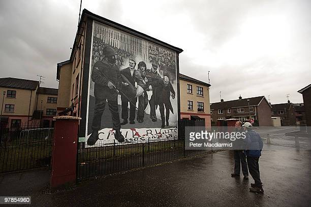 Two men look at a mural remembering the troubles in the Catholic Bogside are of Derry on March 15, 2010 in Northern Ireland. The Bloody Sunday...