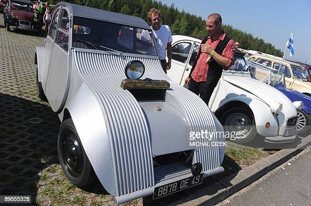 Two men look at a ''scifi'' tuning of a Citroen 2CV on August 1 during the 18th International meeting of Citroen 2CV car fans at the hippodrom in...