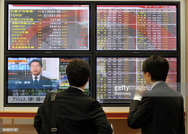 Two men look at a stock prices on screens inside a brokerage in Tokyo, Wednesday, August 10, 2005. Japanese stocks climbed, sending the Topix index...